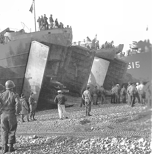 USS LST-515, an unidentified LST and USS LST-54 beached, date and location unknown. LST-54 is unloading a truck.